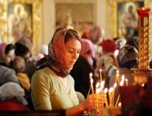 Девушка ставит свечу перед иконой, фото